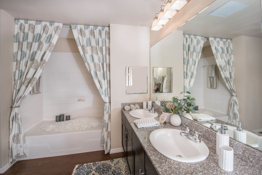 Tiled shower and granite countertop in the master bathroom of a model apartment at Carrington Oaks in Buda, Texas