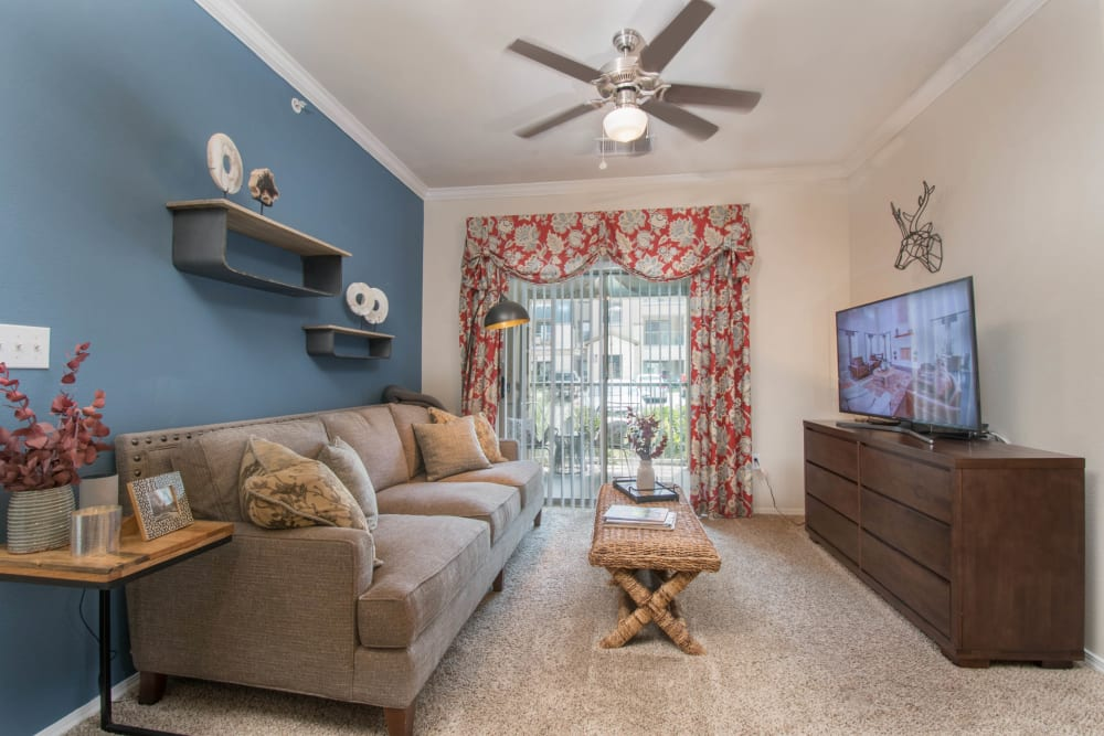 Plush carpeting and a ceiling fan in the living area of a model apartment at Carrington Oaks in Buda, Texas