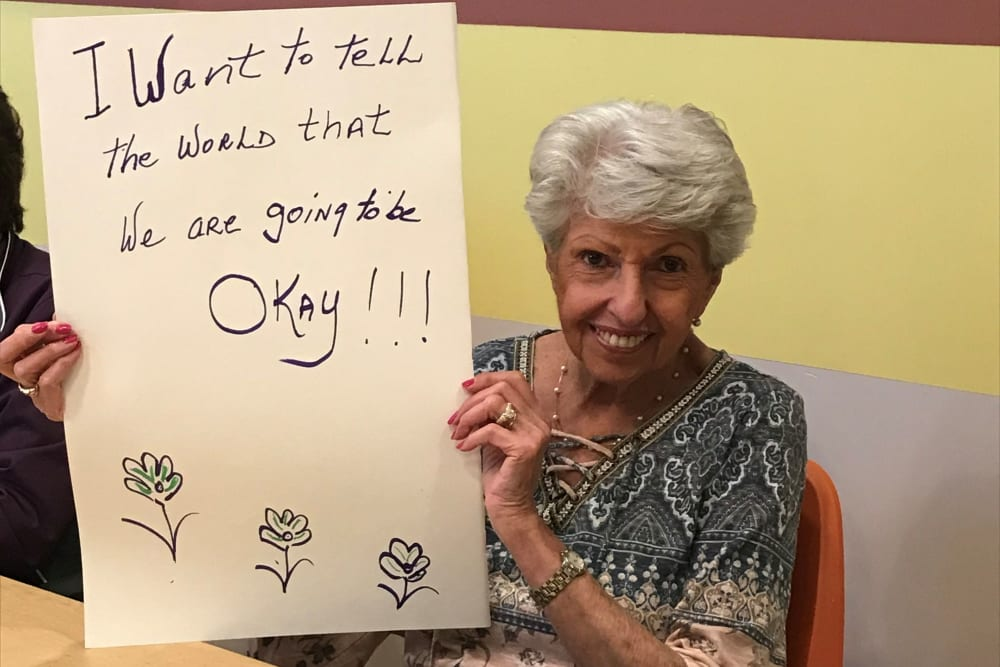 Clearwater resident holding a positive message sign