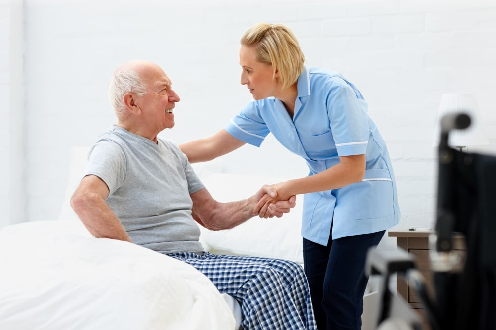 Staff assists resident out of bed at The Atrium in Rockford, Illinois.