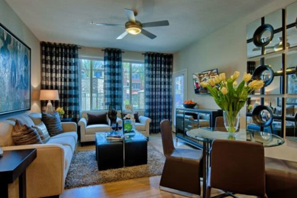 Draped windows and a ceiling fan in the well-furnished living space of a model apartment at Elevation Chandler in Chandler, Arizona
