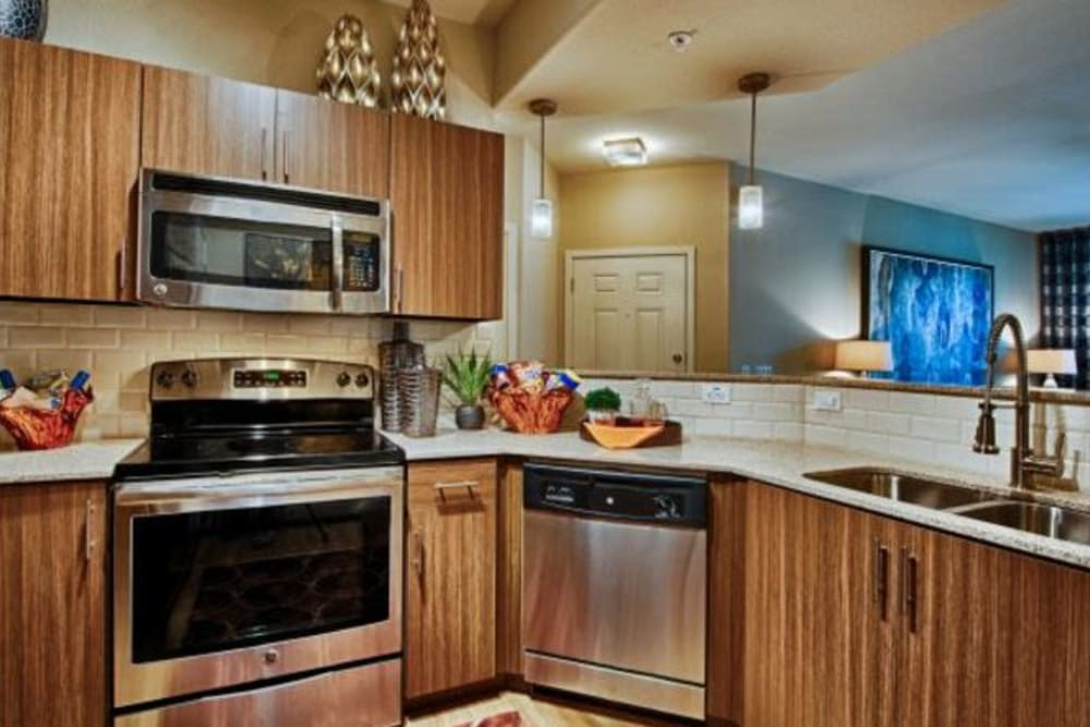 Gourmet kitchen with granite countertops and custom wood cabinetry in a model apartment at Elevation Chandler in Chandler, Arizona