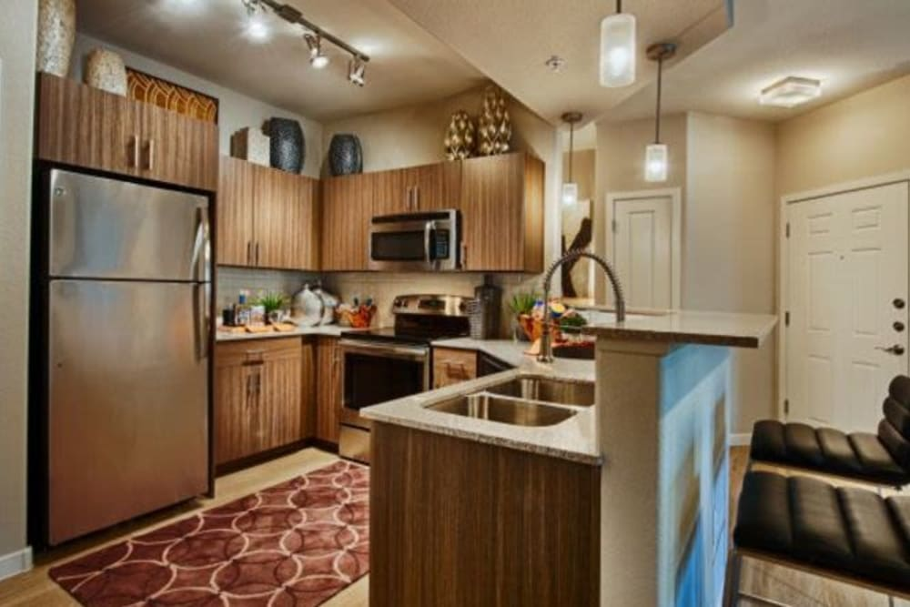 Chef-inspired kitchen with a dual-basin sink and granite countertops in the open-concept layout of a model home at Elevation Chandler in Chandler, Arizona