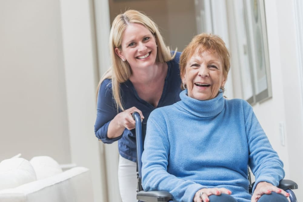 Staff assists resident in a wheelchair at Courtyard Estates at Cedar Pointe in Pleasant Hill, Iowa.