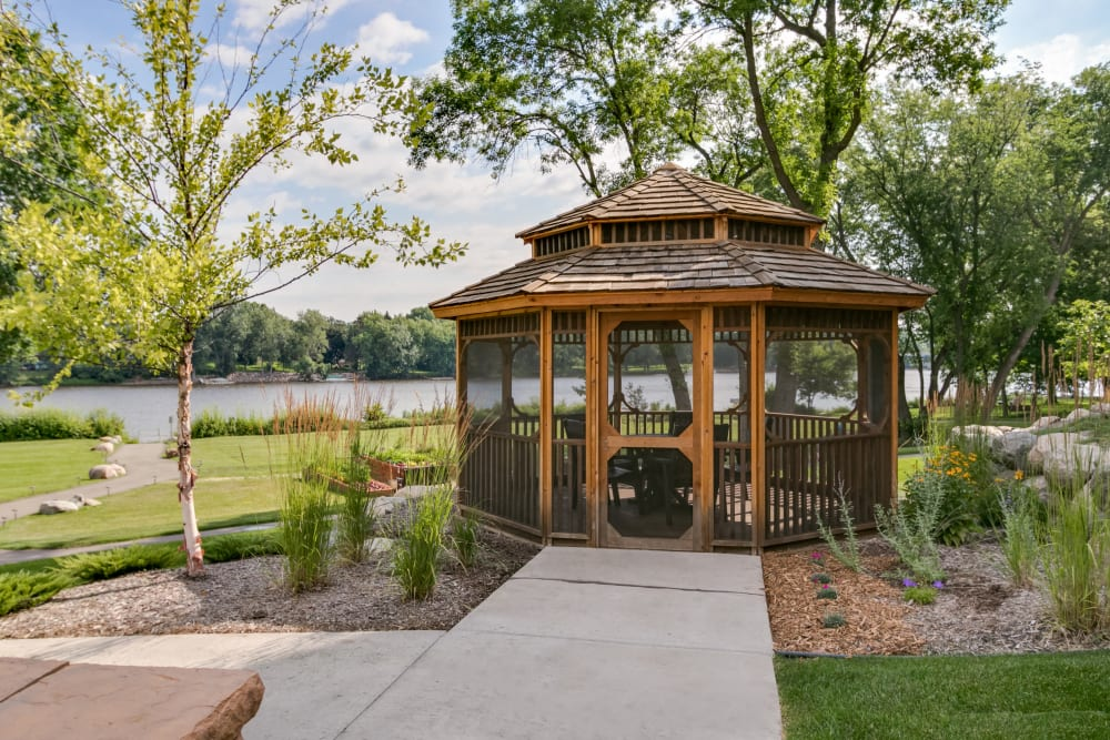Manicured lawns and a gazebo at Applewood Pointe of Champlin in Champlin, Minnesota.
