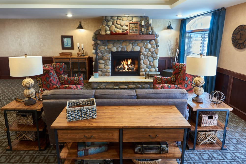 Club room lounge with a fireplace at Applewood Pointe Champlin in Champlin, Minnesota.