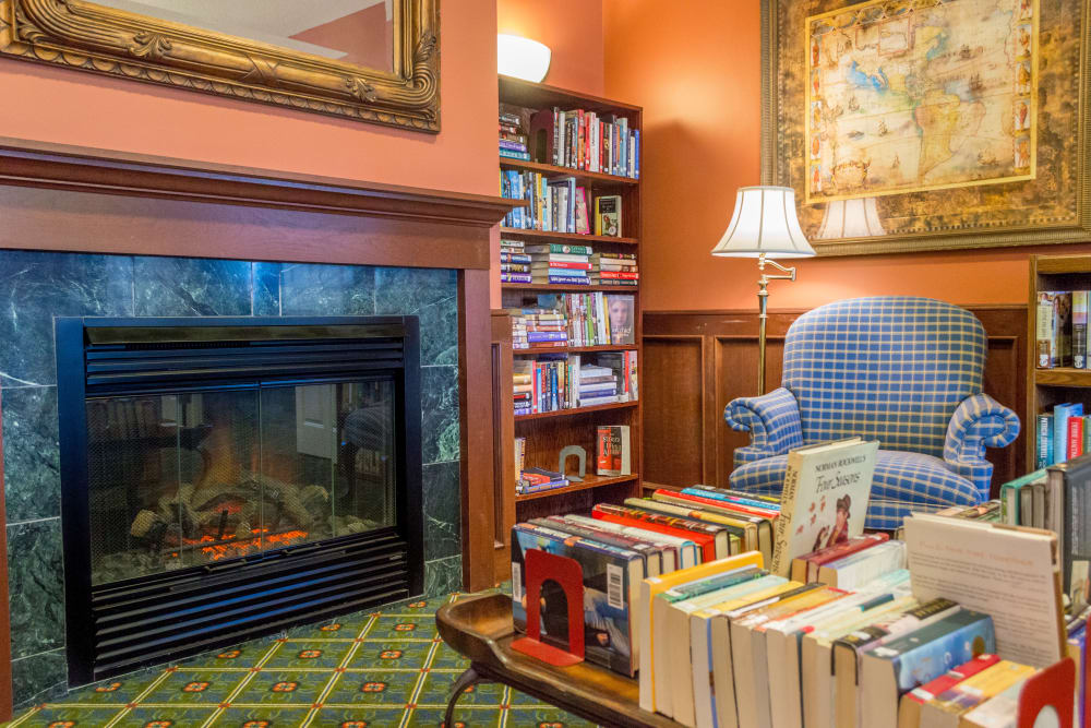 Library with fireplace seating at Applewood Pointe Maple Grove in Maple Grove, Minnesota.