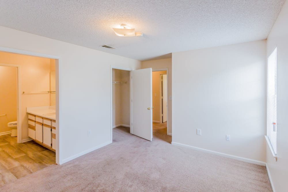 A bedroom with a bathroom and closet at The Retreat at Sherwood in Sherwood, Arkansas