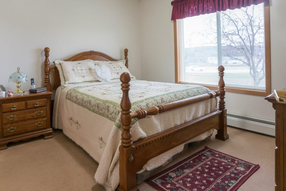 Resident bedroom with a side table at Meadow Lakes Senior Living in Rochester, Minnesota.