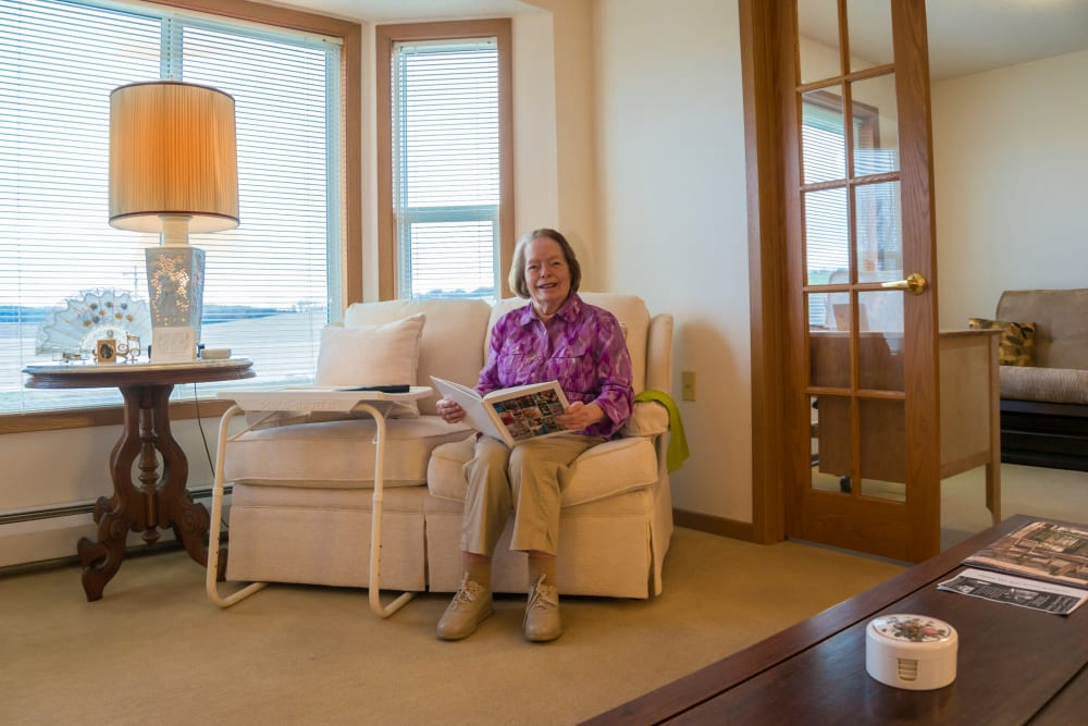 Resident reads a book in her apartment at Meadow Lakes Senior Living in Rochester, Minnesota.