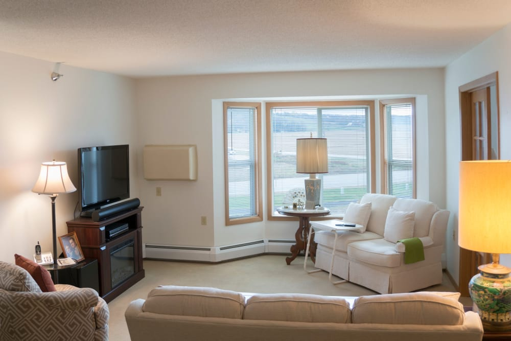 Resident living room with large windows at Meadow Lakes Senior Living in Rochester, Minnesota.