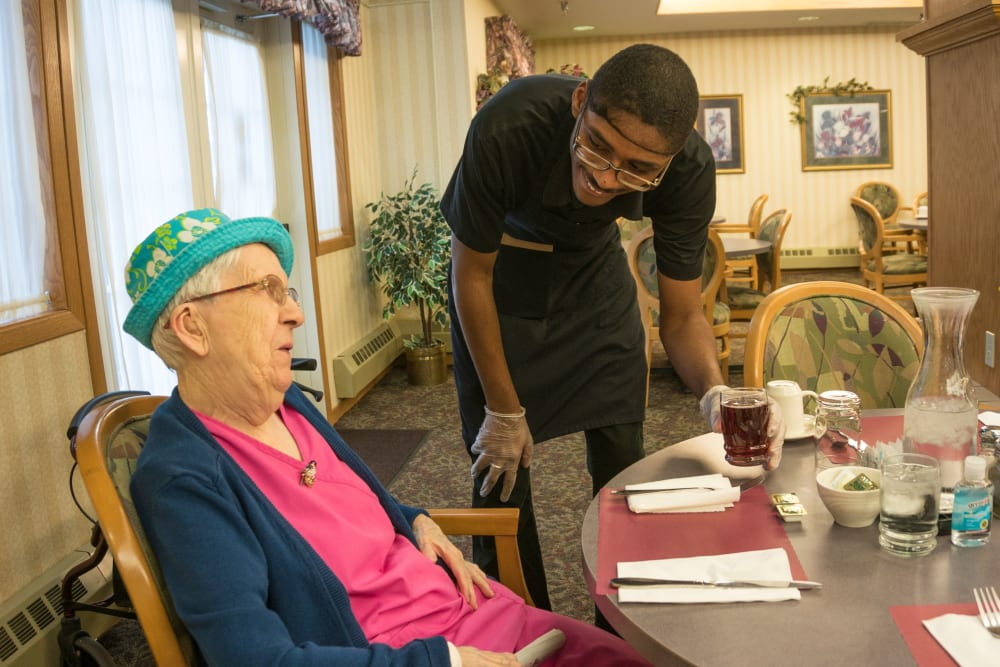 Resident chats with staff in dining room at Meadow Lakes Senior Living in Rochester, Minnesota