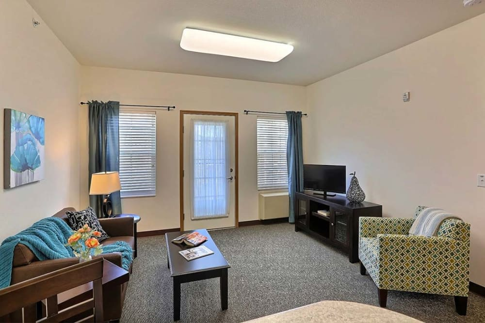 Living room with large windows at Milestone Senior Living in Cross Plains, Wisconsin.