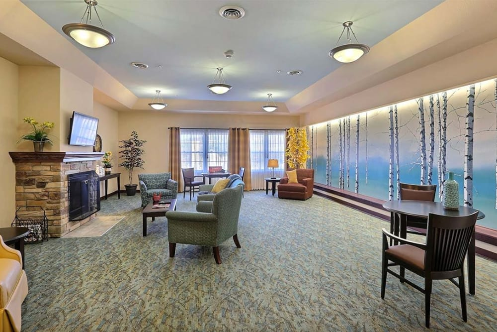 Brightly lit resident lounge with fireplace at Milestone Senior Living in Cross Plains, Wisconsin.