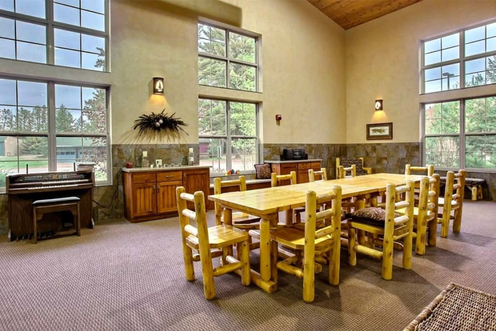 Bright community room with piano at Milestone Senior Living Eagle River in Eagle River, Wisconsin.