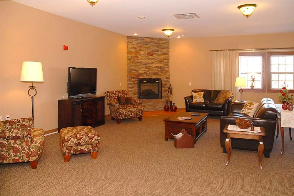 Comfortable resident TV room with fireplace at Milestone Senior Living in Eau Claire, Wisconsin.