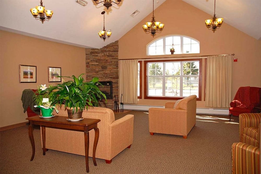 Resident lounge with picture windows and fireplace at Milestone Senior Living in Eau Claire, Wisconsin.