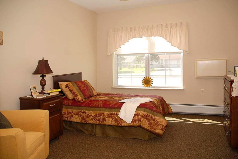Resident bedroom with a side table at Milestone Senior Living in Eau Claire, Wisconsin.