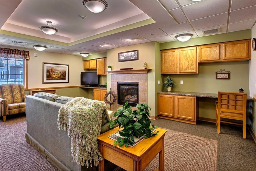 Resident lounge with writing desk and fireplace at Milestone Senior Living in Hillsboro, Wisconsin.