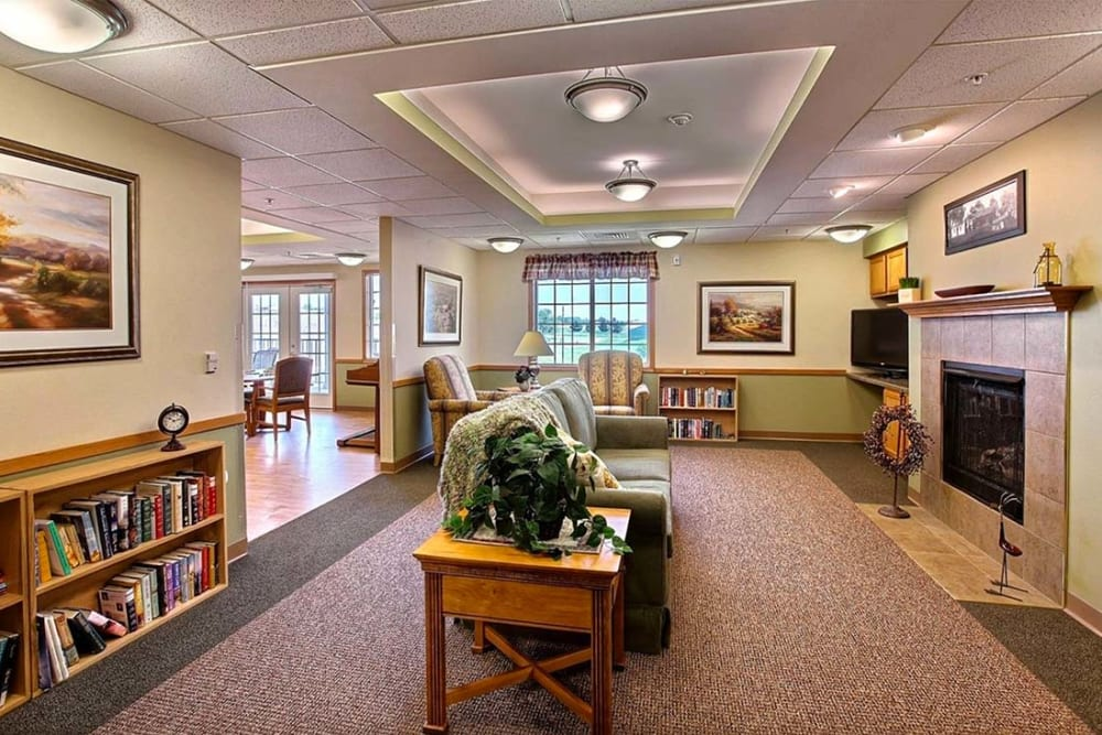 Resident lounge with books and fireplace at Milestone Senior Living in Hillsboro, Wisconsin.
