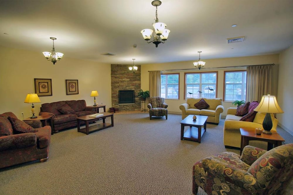 Spacious sitting room with large windows at Milestone Senior Living in Rhinelander, Wisconsin