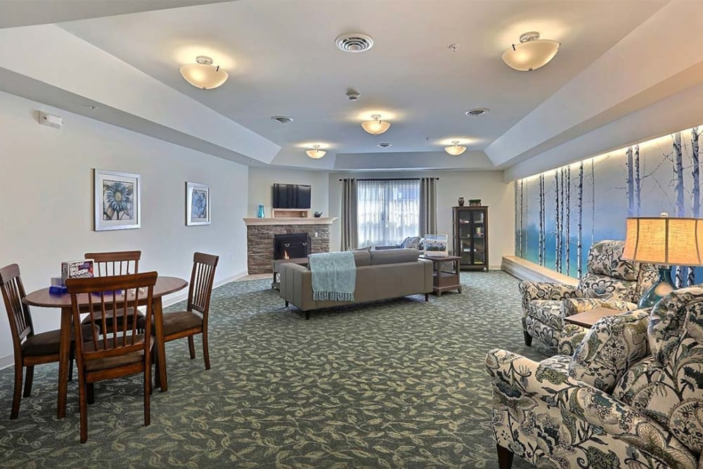 Resident lounge with TV and fireplace at Milestone Senior Living in Stoughton, Wisconsin.