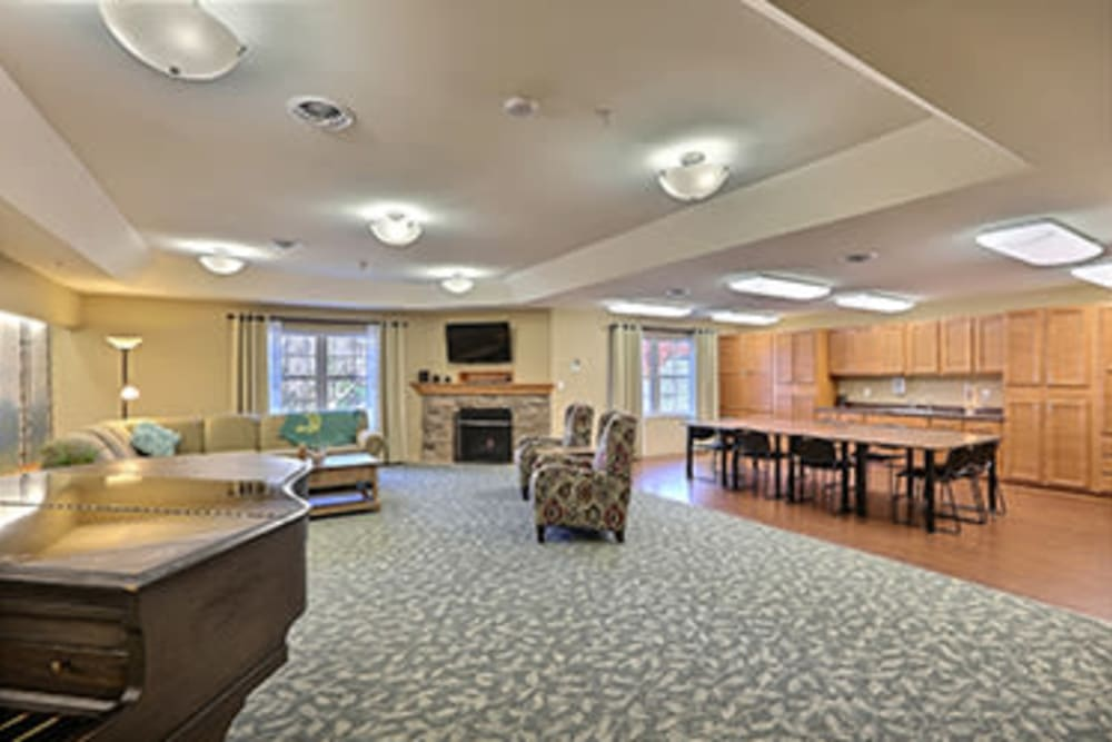Lounge with a piano, TV, and a fireplace at Milestone Senior Living in Tomahawk, Wisconsin
