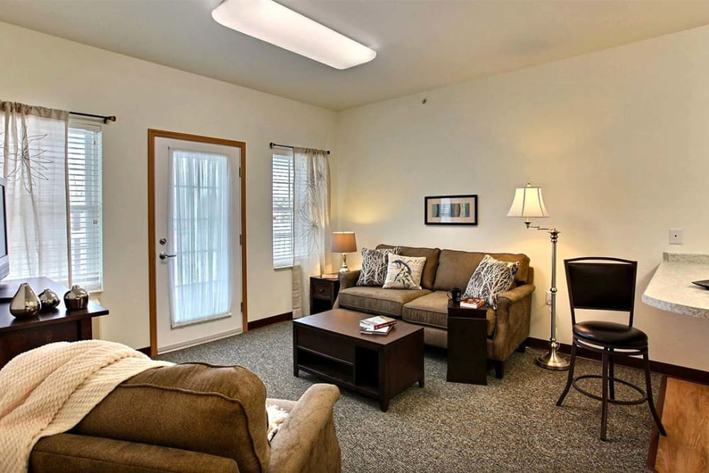 Resident living room with large windows at Milestone Senior Living in Woodruff, Wisconsin.