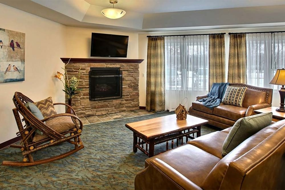 Comfortable common TV room with fireplace at Milestone Senior Living in Woodruff, Wisconsin.