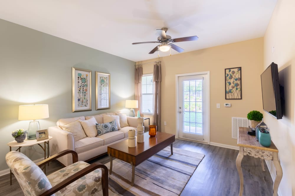 Comfortably decorated living space with a ceiling fan in a model home at Legends at White Oak in Ooltewah, Tennessee