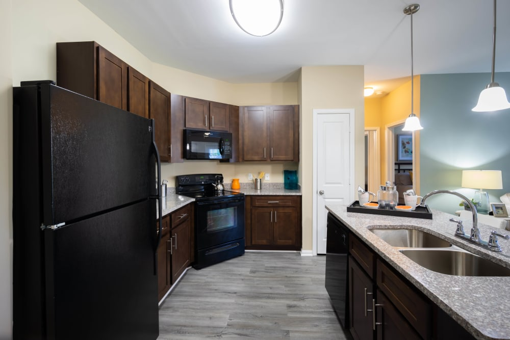 Rich, dark wood cabinetry in a model home's kitchen at Legends at White Oak in Ooltewah, Tennessee
