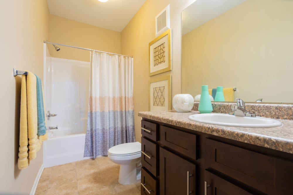 Large master bathroom with a granite countertop in a model apartment at Legends at White Oak in Ooltewah, Tennessee