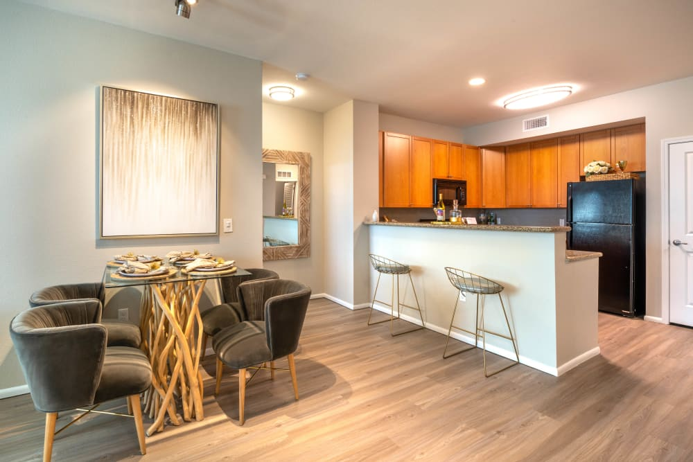 Beautiful hardwood flooring in a model home's dining and kitchen areas at Olympus at Daybreak in South Jordan, Utah