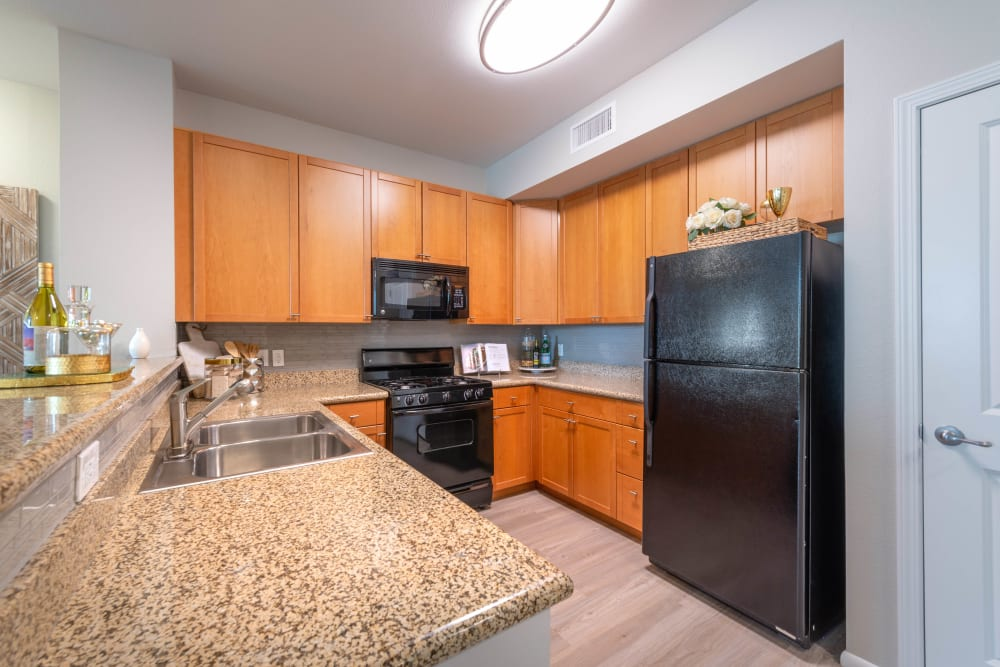 Granite countertops and black appliances in a model home's kitchen at Olympus at Daybreak in South Jordan, Utah