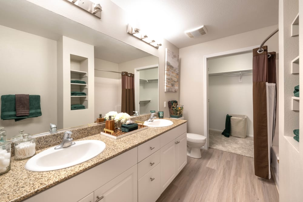 Ample drawer and cupboard storage in a model apartment's master bathroom at Olympus at Daybreak in South Jordan, Utah
