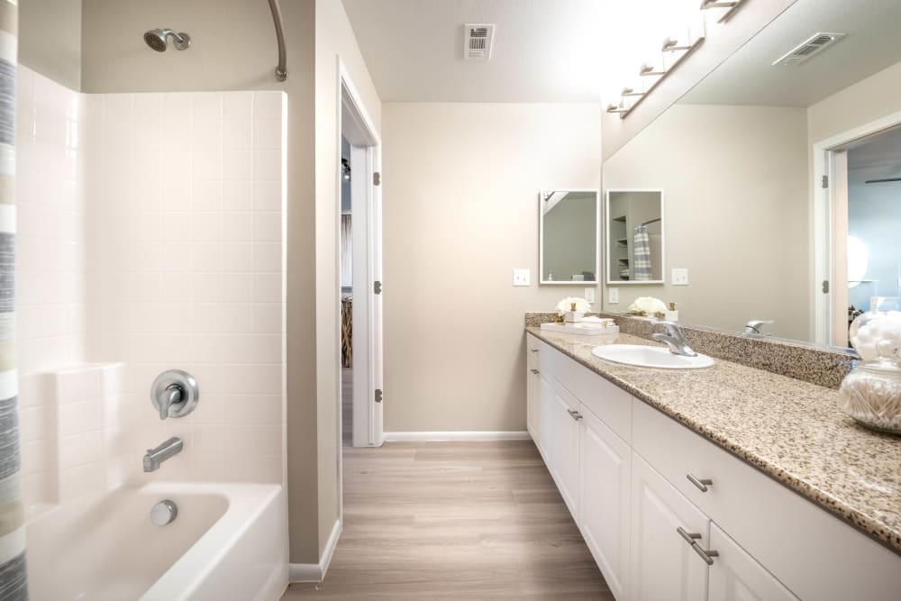 Hardwood flooring and a granite countertop in a model apartment's master bathroom at Olympus at Daybreak in South Jordan, Utah