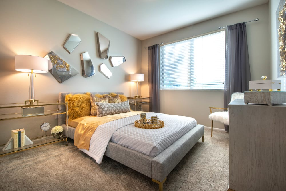 Plush carpeting and draped windows in the master bedroom of a model home at Olympus at Daybreak in South Jordan, Utah