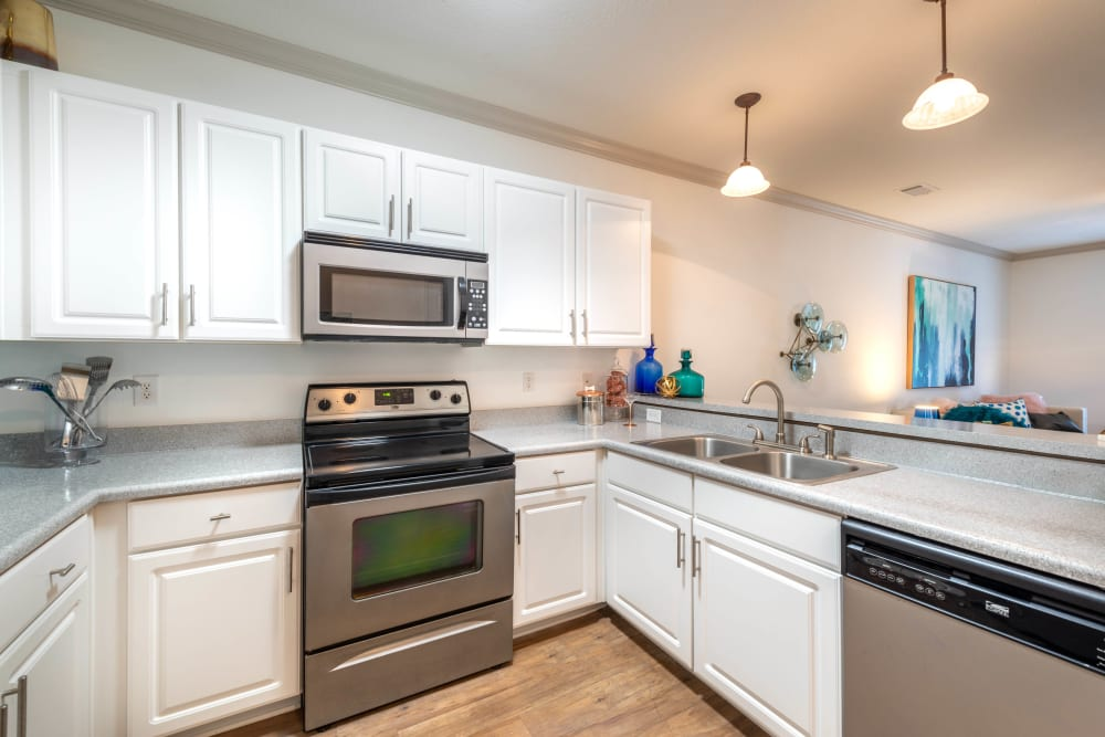 Bright white cabinetry and stainless-steel appliances in a model home's kitchen at Olympus Carrington in Pooler, Georgia