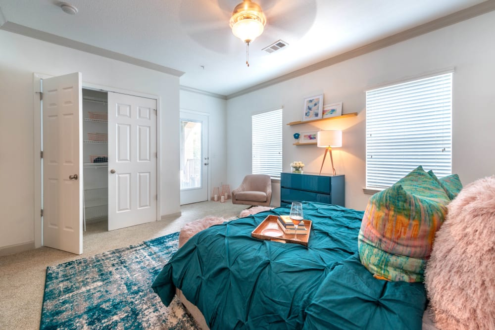 Walk-in closet and large bay windows in a model apartment's master bedroom at Olympus Carrington in Pooler, Georgia