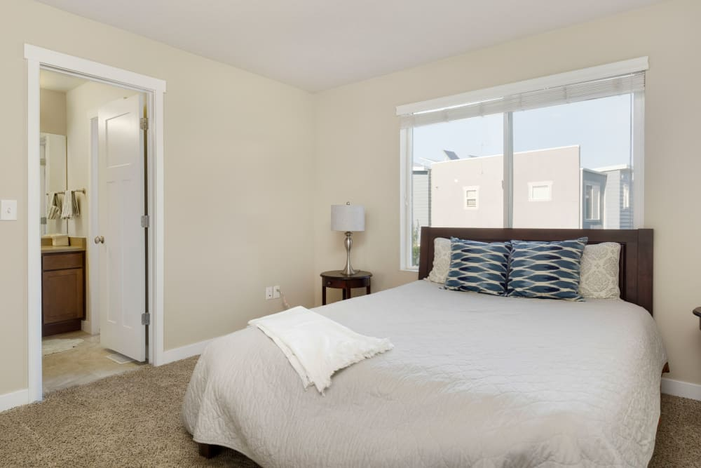 Well-lit bedroom with large bathroom at Olympus at the District in South Jordan, Utah