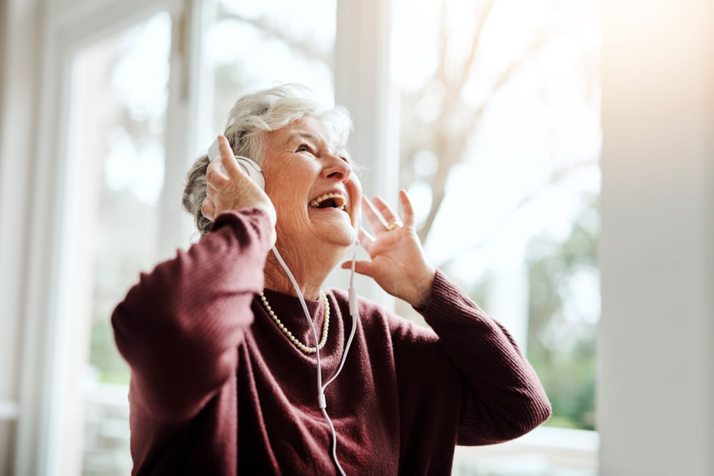 Resident enjoying music over headphones in an apartment at The Preserve of Roseville in Roseville, Minnesota.