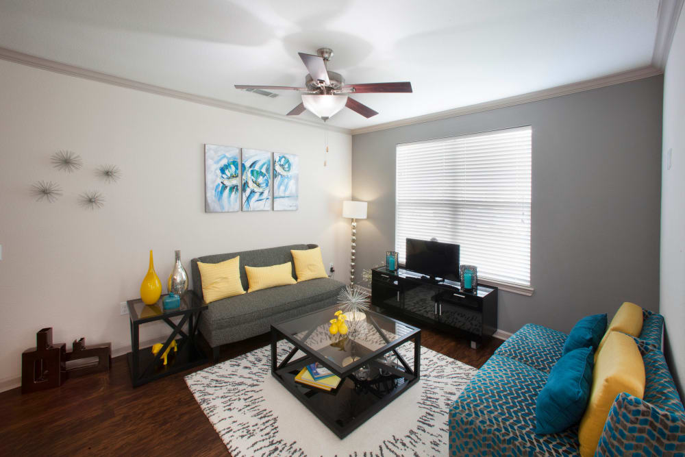 Comfortably decorated model home's living space with a ceiling fan at Olympus Katy Ranch in Katy, Texas