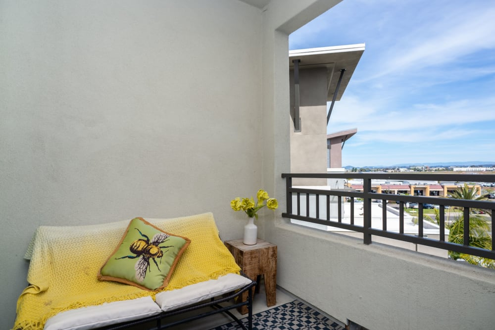 Comfortably furnished private balcony outside a model home at Olympus Corsair in San Diego, California