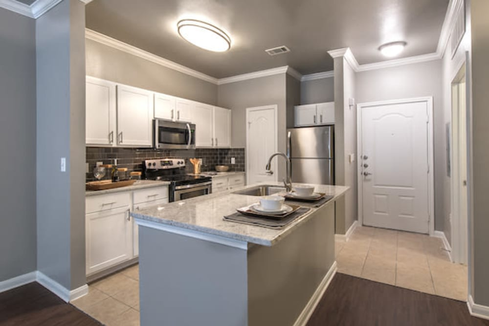 Model home's gourmet kitchen with granite countertops and stainless-steel appliances at Olympus Las Colinas in Irving, Texas