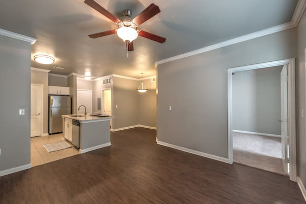 Rich hardwood flooring and a ceiling fan in a model home's open-concept living areas at Olympus Las Colinas in Irving, Texas
