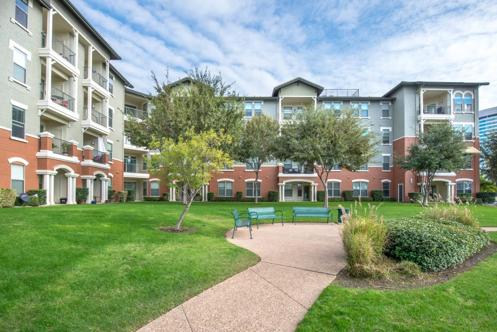 Beautifully maintained landscaping and green spaces outside resident buildings at Olympus Las Colinas in Irving, Texas