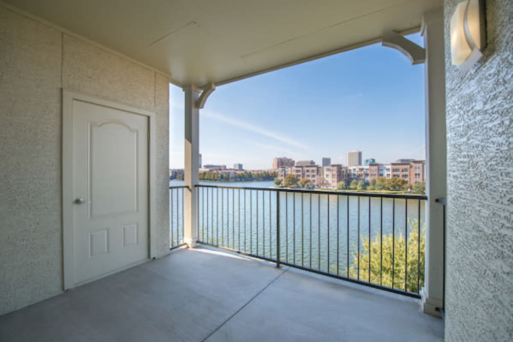 Private balcony with a view of the lake outside a model home at Olympus Las Colinas in Irving, Texas