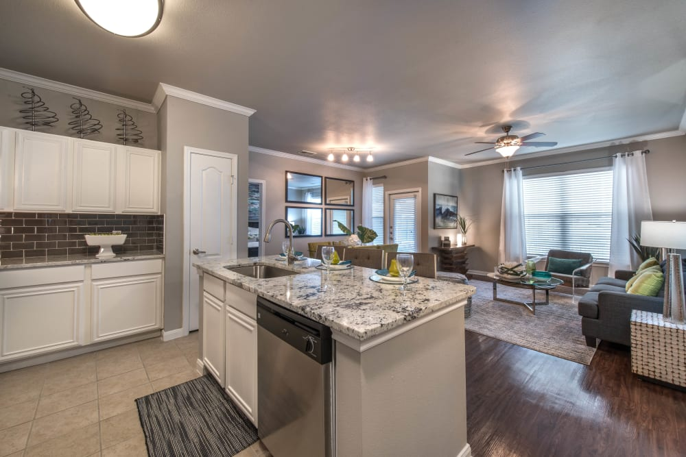 Open-concept gourmet kitchen with granite countertops in a model home at Olympus Las Colinas in Irving, Texas