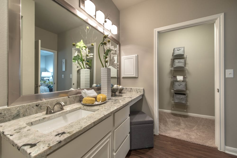 Master bathroom with a granite countertop and hardwood flooring in a model home at Olympus Las Colinas in Irving, Texas