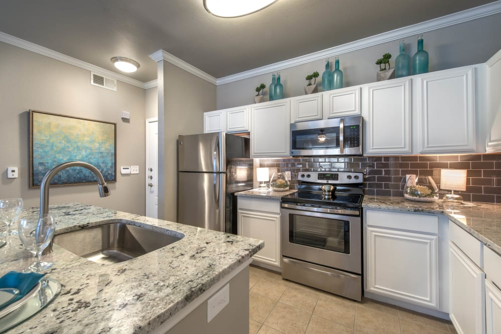 Model apartment kitchen with stainless-steel appliances and white cabinetry at Olympus Las Colinas in Irving, Texas